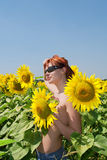 Red-hair girl sunbathing among sunflowers Royalty Free Stock Images
