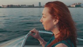 Red hair girl in turquoise dress drive motor boat. Summer evening. Romantic. stock footage