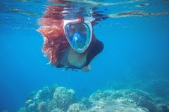 Red hair girl underwater in tropical sea. Snorkel in full face mask. Stock Photography
