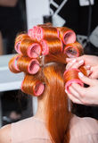 Red hair during hair dressing with curler Stock Photos