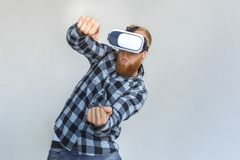 Freestyle. Mature man in virtual reality headset standing isolated on grey driving imaginary car grimacing playful. Red hair mature man wearing virtual reality stock images