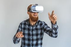 Freestyle. Mature man in virtual reality headset standing isolated on grey pointing at space close-up. Red hair mature man wearing virtual reality headset royalty free stock photos