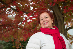 Red Hair Senior Lady Under the Tree Looking at you Happily Stock Images