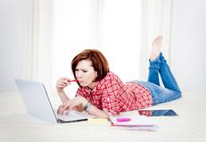 Red hair student, business woman lying down working on laptop Royalty Free Stock Photo