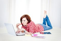 Red hair student, business woman lying down working on laptop Stock Photo