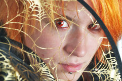 Red-hair witch looking through spider's web Royalty Free Stock Images