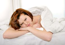 Red hair woman on bed waking up with hangover and headache Royalty Free Stock Images