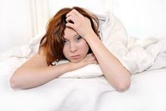 Red hair woman on bed waking up with hangover and headache Stock Photos