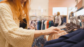 Red hair woman in a clothing store chose a dress - shopping concept. Close up Stock Photo