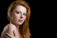 Red hair woman face. Natural face of a caucasian woman with red hair and brown eyes. Over a black background Royalty Free Stock Photos