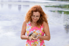 Red hair woman looking on couple of snails Royalty Free Stock Images