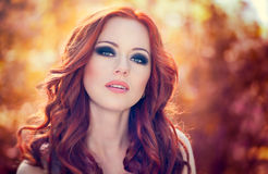 Red hair woman. Outdoors portrait of beautiful woman with red hair and smoky eyes makeup royalty free stock photos