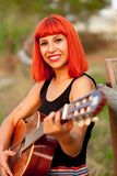 Red hair woman playing guitar Stock Images