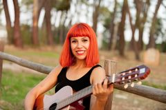 Red hair woman playing guitar Stock Photography