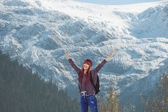 Red-hair woman raising her arms in front of snow-covered mountains background. Digital composite of Red-hair woman raising her arms in front of snow-covered Stock Photo
