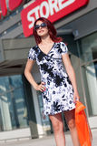 Red hair woman with shopping bag against of store Royalty Free Stock Images