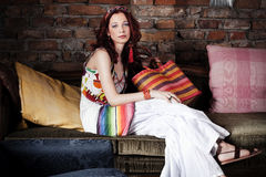 Red hair woman in summer clothes resting on sofa Stock Images