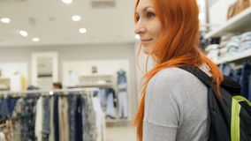 A red hair woman walking among dresses in clothes store. Rear view Stock Photo
