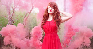 Red hair woman wearing dress surrounded by smoke Royalty Free Stock Photos