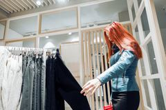 Red hair young girl in a blue leather jacket chooses pants for sale stock photography