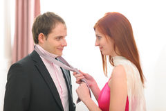 Red hair young woman helping tie necktie. Young women helping tie necktie Royalty Free Stock Images