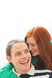 Red hair young woman whispering in boyfriends ear Stock Image