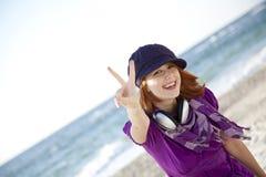 Red-haired девушка с наушниками на пляже. стоковое фото rf