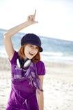 Red-haired девушка с наушниками на пляже. стоковая фотография