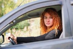 Red-haired женщина управляя автомобилем стоковое фото