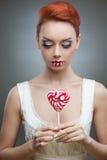 Red-haired конфета удерживания девушки стоковые фото