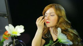 Red-haired actress in the dressing room makes eye makeup with blue shadows preparing to go on stage. Close-up stock video footage