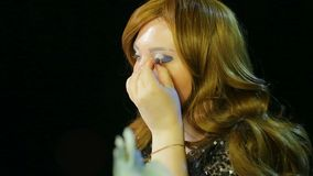 Red-haired actress in the dressing room makes eye makeup with blue shadows preparing to go on stage. Close-up stock video
