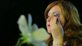 Red-haired actress in the dressing room makes eye makeup with blue shadows preparing to go on stage. Close-up stock footage