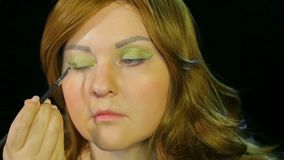 Red-haired actress in the dressing room makes eye makeup green shadows preparing to go on stage. Close-up stock video footage