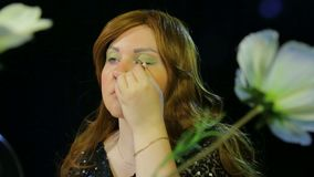 Red-haired actress in the dressing room makes eye makeup green shadows preparing to go on stage. Close-up stock video