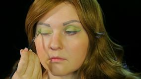 Red-haired actress in the dressing room makes eye makeup green shadows preparing to go on stage. Close-up stock footage
