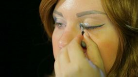 Red-haired actress in the dressing room makes eye makeup with silver shadows preparing to go on stage. Close-up stock video footage