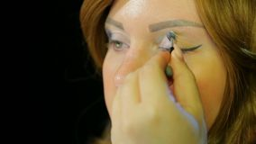 Red-haired actress in the dressing room makes eye makeup with silver shadows preparing to go on stage. Close-up stock video