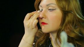 Red-haired actress in the dressing room makes eye makeup with silver shadows preparing to go on stage. Close-up stock footage