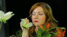 Red-haired actress in the dressing room makes eye makeup with silver sparkles preparing to go on stage. Close-up stock video footage