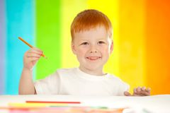Red-haired adorable boy on rainbow background Stock Image