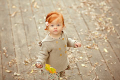Red-haired baby girl on the background of autumn nature.  Royalty Free Stock Photography