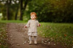 Red-haired baby girl on the background of nature in a forest in. Autumn Stock Images