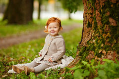 Red-haired baby girl on the background of nature in a forest in. Autumn Stock Photography