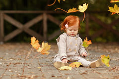 Red-haired baby girl on the background of nature and sitting in. The fall leaves Royalty Free Stock Image