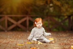 Red-haired baby girl on the background of nature and sitting in. The fall leaves Royalty Free Stock Images