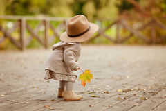 Red-haired baby girl wearing a hat outdoors in autumn.  stock photo