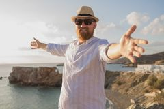 Red-haired bearded hipster traveler man with open hands is standing with his back to the sea and smiling in the rays of the mornin. G sun. Redhead bearded Royalty Free Stock Image