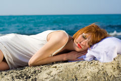 The red-haired  beautiful girl sleeps at the sea Stock Photo