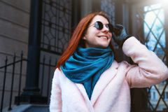 Red haired beautiful girl is walking by the street in a pink coat and blue scarf, with sunglasses. Royalty Free Stock Photos